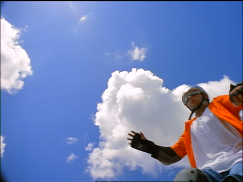 slow motion low angle man on inline skates jumping over camera with blue sky + clouds above