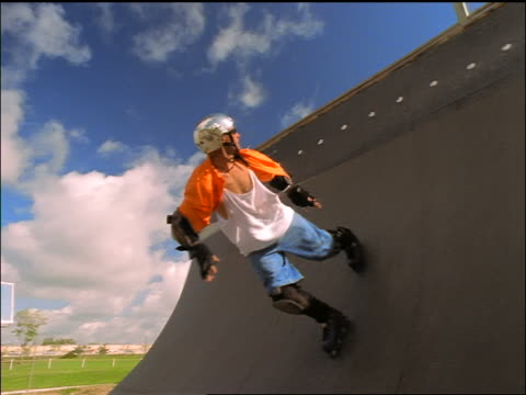 slow motion low angle man on inline skates performing spinning stunt on half-pipe ramp