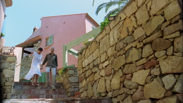 Slow motion low angle medium shot couple walking down stairs holding hands / Corsica