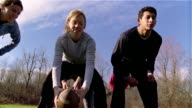 Slow motion low angle medium shot pan men and women playing football/ Maine