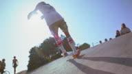 1976 slow motion low angle medium shot teenage boy in tube socks turning up slope on skateboard