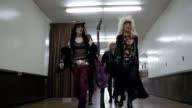 Slow motion low angle medium shot tracking shot glam band walking in hallway backstage / raising their instruments