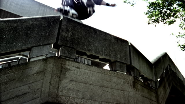 Slow motion low angle medium shot two freerunners jumping off stairwell onto roof