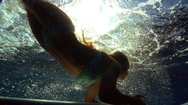 Slow motion low angle medium shot woman diving onto surfboard beneath surface of water / Tahiti