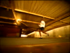 SEPIA slow motion low angle tracking shot PAN Black male athlete running + shadow boxing on floor edge in large warehouse