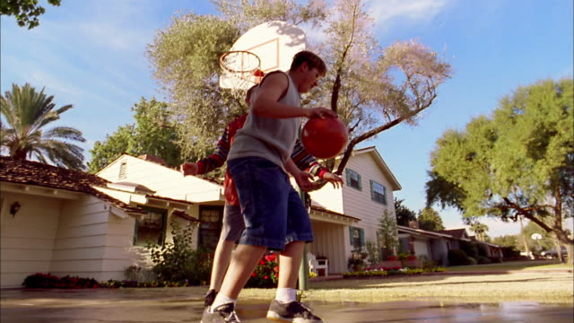 Slow motion low angle two boys playing one-on-one basketball in suburban driveway / Phoenix, Arizona