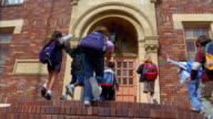 Slow motion low angle wide shot children running up stairs to school with teacher opening and closing door