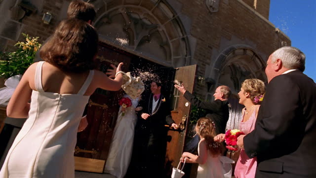 Slow motion low angle wide shot guests throwing rice onto bride and groom coming out of church