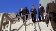 Slow motion low angle wide shot pan business people walking up and down stairs / talking