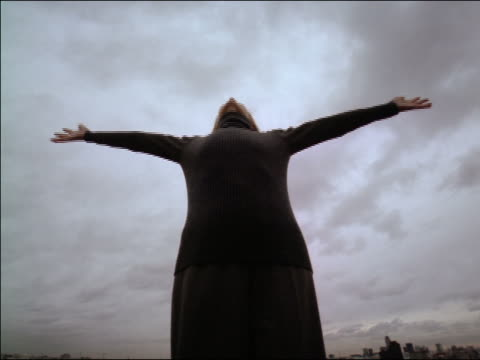 slow motion low angle woman in black with arms spread out + head tilted back falling backwards / cloudy sky