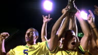 slow motion low angle MS zoom in zoom out tilt up PAN soccer team holding up trophy cup + cheering on stadium field at night