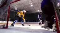 slow motion male hockey player receiving pass + shooting goal as REAR VIEW goalie attempts to stop