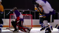 slow motion MS male ice hockey goalie attempting to stop goal + failing / zoom in other team hug + celebrate