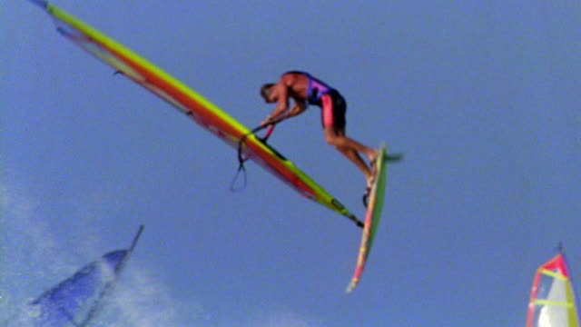 slow motion male windsurfer jumping off wave, doing flip in air + wiping out / Hawaii