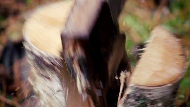 Slow motion: Man chopping wood. Close up