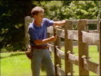slow motion man hammering nail on rail fence / hits thumb + shakes hand in pain