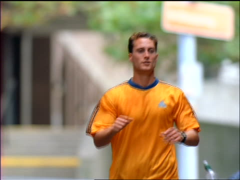 slow motion man in orange shirt jogging towards camera as person hands him water bottle