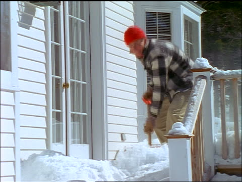 slow motion man in red cap shoveling snow on deck of house