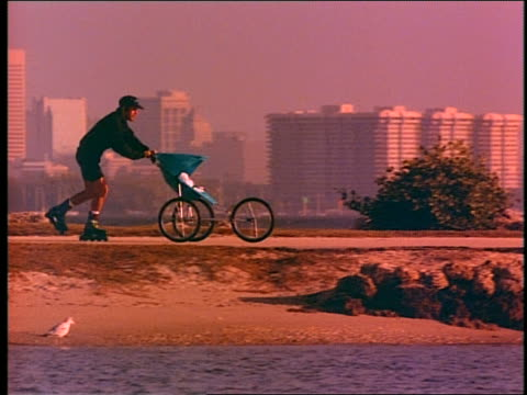 slow motion PAN man inline skating past ocean while pushing baby carriage / city skyline in background