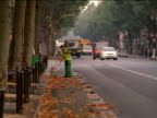 slow motion man sweeping leaves on side of street lined by trees with oncoming traffic / Paris, France