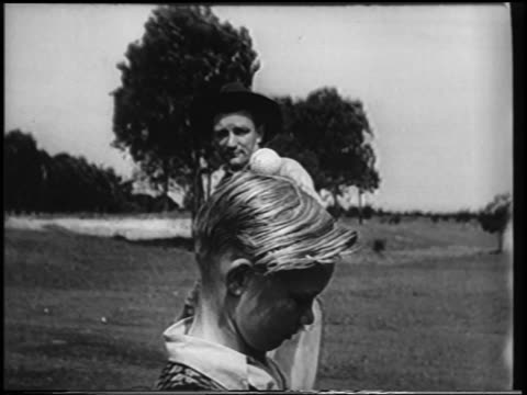 B/W 1951 slow motion man with bullwhip whipping ball from the top of boy's head / newsreel
