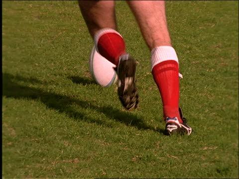 slow motion man's legs kicking ball in rugby match
