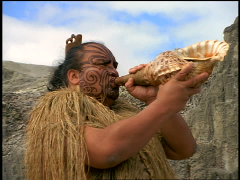 slow motion Maori Haka performer blowing through conch shell + turning / Rotorua / N.Island / New Zealand