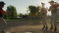Slow motion medium panning shot of baseball player scoring / American Fork, Utah, United States