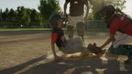 Slow motion medium panning shot of baseball runner safe at home plate / American Fork, Utah, United States