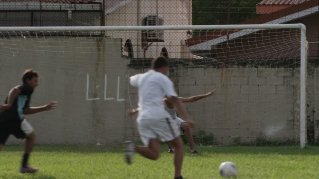 Slow motion medium panning shot of soccer team playing on field / Esterillos, Puntarenas, Costa Rica