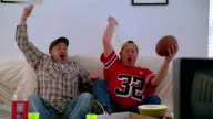 Slow motion medium shot 2 men watching football on TV / standing up cheering and waving towels / high fiving