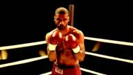 Slow motion medium shot Black boxer in corner of ring throwing punches at camera
