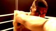Slow motion medium shot Black boxer in ring sparring with camera