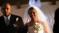 Slow motion medium shot Black bride and her father walking down aisle