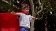 Slow motion medium shot crane shot small boy in superhero costume pretending to fly