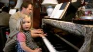 Slow motion medium shot man giving daughter piano lesson / girl looking at CAM