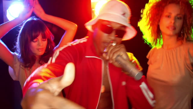 Slow motion medium shot man in track suit and hat singing into microphone, two young women dancing behind him