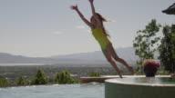 Slow motion, medium shot of girl jumping into swimming pool / Cedar Hills, Utah, United States