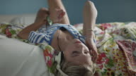 Slow motion medium shot of teenage girl listening to music with headphones on bed / Sandy, Utah, United States