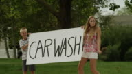 Slow motion medium shot of waving placard advertising car wash / Pleasant Grove, Utah, United States