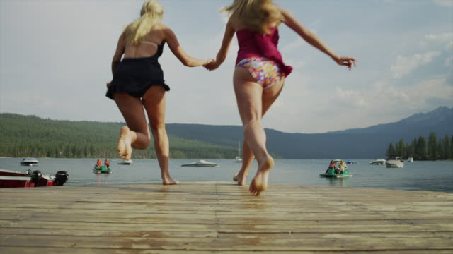 Slow Motion medium shot of young women running from dock into lake / Redfish Lake, Idaho, United States