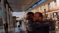 Slow motion medium shot pan Black couple greeting and hugging each other at airport