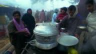 Slow motion medium shot pan men cooking and serving food from pots at outdoor market in fog / Varanasi, India