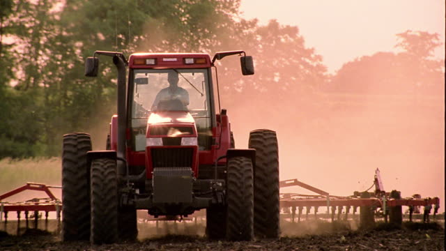Slow motion medium shot pan person driving tractor and dragging plow across field towards camera / Clarksville, Iowa