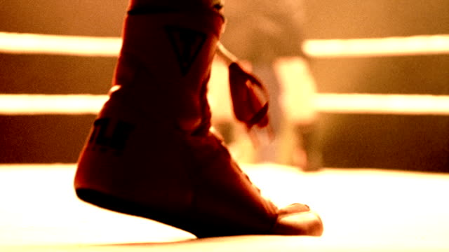 Slow motion medium shot pan selective focus boots of boxers jumping on canvas in ring / opponent in background