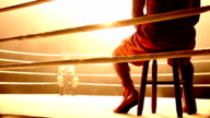 Slow motion medium shot pan selective focus boxers sitting in opposite corners of ring facing each other