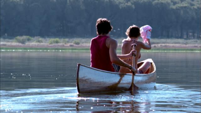 Slow motion medium shot rear view man and woman rowing in canoe on lake / woman removing shirt over bikini