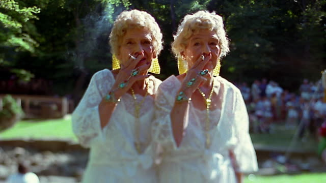 Slow motion medium shot senior female twins smoking cigarettes / wearing identical white gowns / laughing