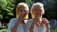 Slow motion medium shot senior female twins smoking cigarettes / wearing identical white gowns / blowing smoke