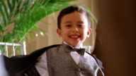 Slow motion medium shot small Hispanic boy in tuxedo dancing / turning away